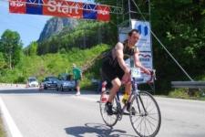 Teilnehmer des Kesselbergrennens passiert mit dem Rennrad die am Start wartenden E-Mobile